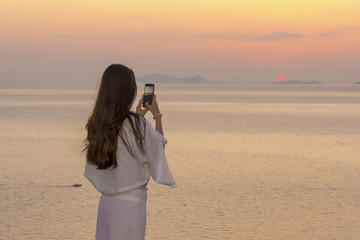 beautiful brunette taking pictures of the sunset in Santorini. Girl in transparent white dress makes the photograph
