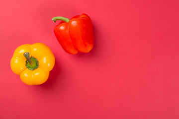 Top view of bright yellow and red bell peppers paprika on red background.