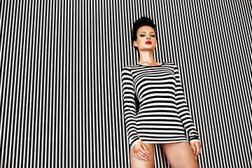 Wall Mural - Sexy and beautiful woman in striped dress on striped background. Fashion model posing concept