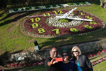 Tourists pose for a selfie with a clock of flowers in the background in Vina del Mar