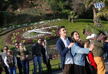 Tourists pose for pictures with a clock of flowers in the background in Vina del Mar
