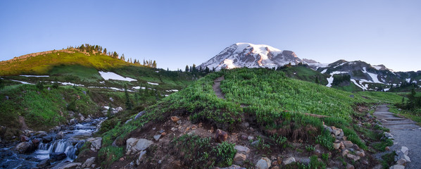 Mt. Rainier panorama at sunrise. Waterfall, paths and wildflowers in the foreground. Location: Mt. Rainier National Park in Washington state