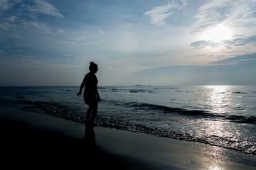 Womand with Tropical sunset on the beach Prachuap Khiri Khan. Thailand