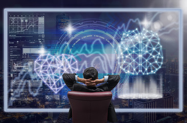 Back side of sitting businessman who is looking at the technology digital virtual screen over the cityscape and heart with brain shape background, Business and technology concept