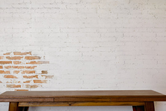 Mock up wooden table with white brick wall. For product display montage..