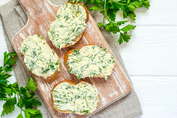 Sandwiches with herbs butter On Cutting board on white wooden background