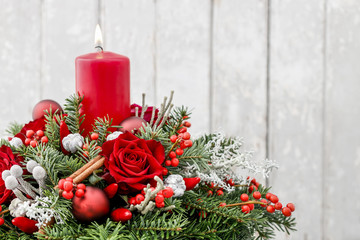 Christmas decoration with candle, red roses, fir, brunia and cinnamon sticks.