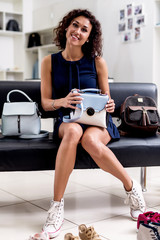 Portrait of young smiling female shopper sitting with a new handbag on her laps in accessories shop