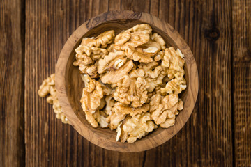 Portion of Cracked Walnuts on wooden background (selective focus)