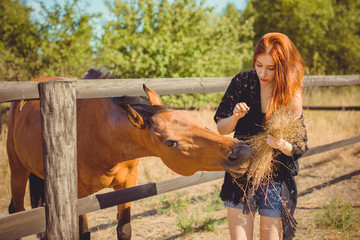 Young red hair beautiful girl having fun with horse on the farm. Woman in Boho looks likes horse is eating in nature. Pretty and natural adult woman outdoors