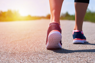 young girl in running shoes runs along road, only her legs are visible, legs and sneakers, sunlight