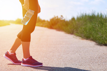 Girl holds sports bottle with water for drinks, legs and sneakers, sunlight