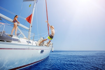 Boy with his sister jump of sailing yacht on summer cruise. Travel adventure, yachting with child