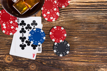 On an old wooden table, play poker and drink alcohol