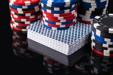 Cards and chips for playing poker are reflected on a black background