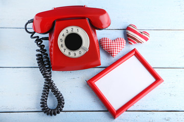 Red retro telephone with photo frame and hearts on white wooden table