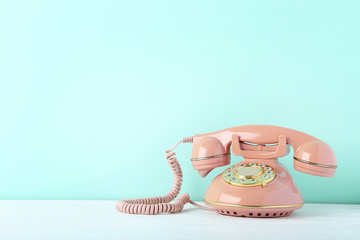 Pink retro telephone on white wooden table