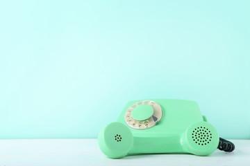 Green retro telephone on white wooden table