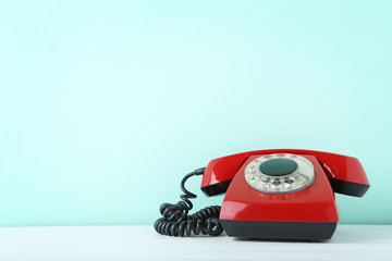 Red retro telephone on white wooden table