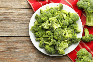 Broccoli in plate with napkin on grey wooden table