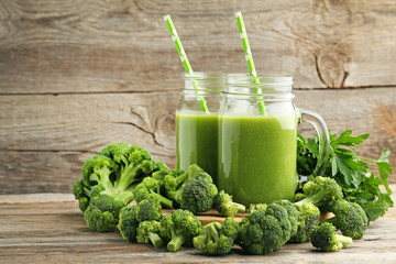 Bottles of juice with broccoli and parsley on grey wooden table