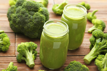Bottles of juice with broccoli on brown wooden table