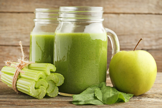 Bottles of juice with celery and apple on grey wooden table