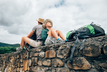 Father and son backpacker traveler rest together sitting on old stone wall