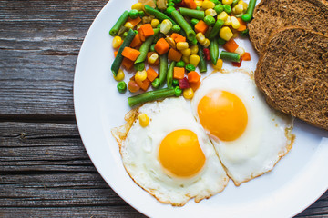 two fried eggs on the plate and vegetables