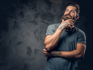 A man with tattooed arms over dark grey background.