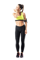 Athletic sporty female jogger in sportswear warm up stretching neck muscles. Full body length portrait isolated on white background.