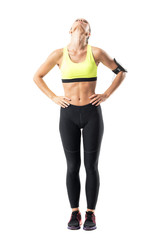 Sporty female jogger stretching neck muscles with head titled back. Full body length portrait isolated on white background.
