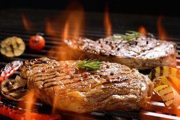Wall Mural - Grilled pork steak with vegetable on the flaming grill