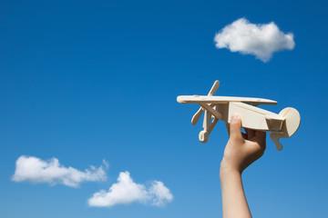 Wooden plane in child hand.