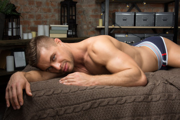 Naked sexy guy on the bed. House. Rest and relaxation.