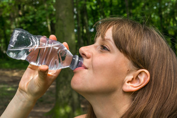 Woman is drinking bottle of water at hot summer day