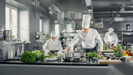 Photo sur Plexiglas Cuisine Famous Chef Works in a Big Restaurant Kitchen with His Help. Kitchen is Full of Food, Vegetables and Boiling Dishes.