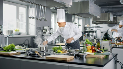 Famous Chef Works in a Big Restaurant Kitchen with His Apprentices. Kitchen is Full of Food, Vegetables and Boiling Dishes.