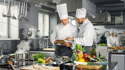 Two Famous Chefs Discuss Their Video Blog while Using Tablet Computer. They Work on a Big Restaurant Stainless Steel Professional Kitchen.
