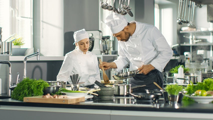 Famous Chef and His Female Apprentice Prepare Special Dish in a Modern Five Star Restaurant's Kitchen.