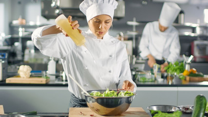 In a Famous Restaurant Female Cook Prepares Salad, ads Oil. She Works in a Big Modern Kitchen.