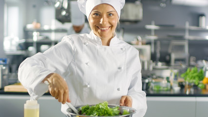 In a Famous Restaurant Female Cook Prepares Salad and smiling on a camera. She Works in a Big Modern Kitchen.