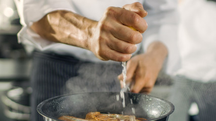 Professional Chef Squeezes Lemon Juice onto Hot Pan with Red Fish Fillet on it. He Works in a Modern Kitchen.