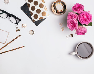Woman's workplace with gold accessories, coffee and beautiful roses