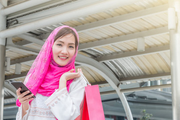 Very happy beautiful young woman in casual clothing with shopping bags in downtown with building background