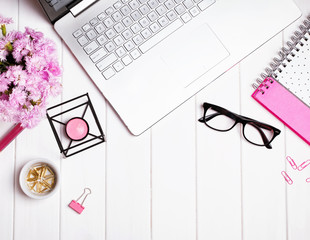 Woman's workplace with stylish accessories and flowers