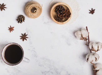 Coffee, cotton branch and other small objects on marble background