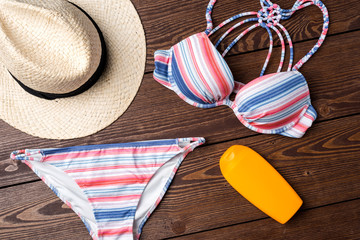 Female swimsuit with beach accessories on wooden background