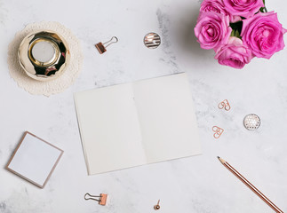Blank notepad, pink roses and small golden accessories