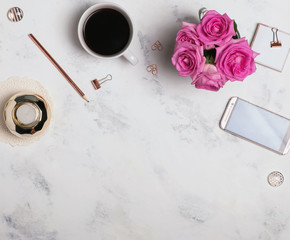 Woman's workplace with coffee, phone and roses